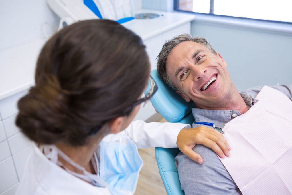 a middle aged man sitting in a dental chair and smiling at the dentist
