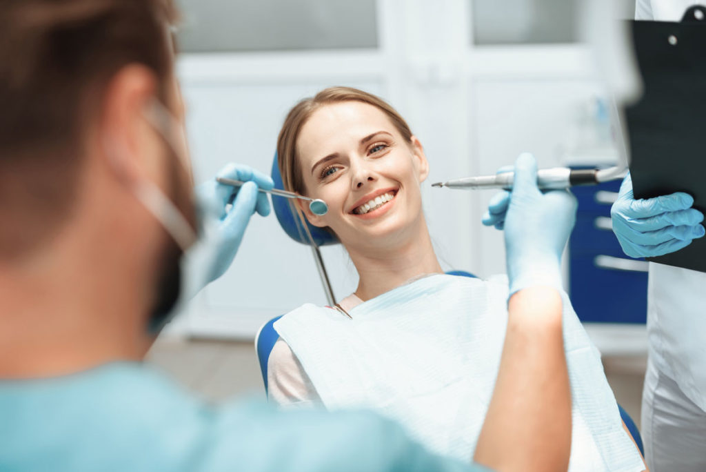 a female patient sitting in an exam room at the dentist office
